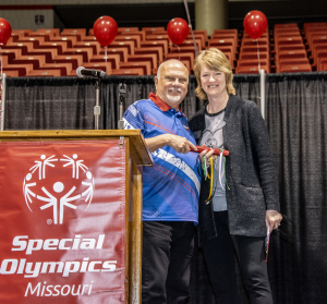 Two SOMO staff members pose together at the side of the Special Olympics Missouri podium