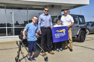 Athletes pose in front of silver jeep with car dealers