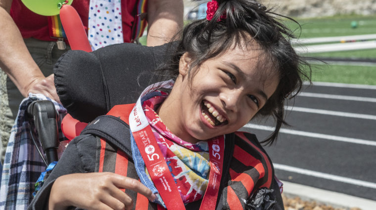 An athlete in a wheelchair wears a medal and smiles at the camera