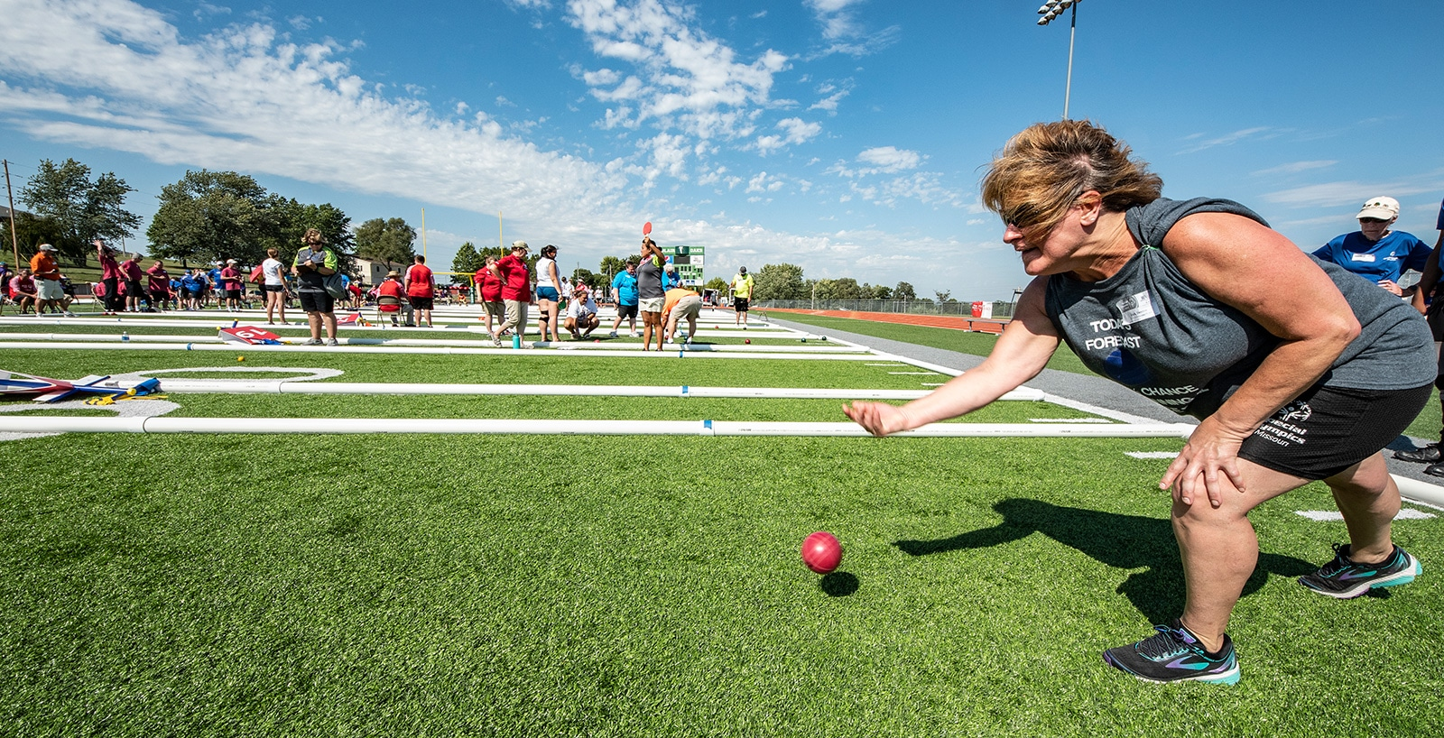 An athlete releases a bocce ball to roll down a turf field with many other bocce courts in the background
