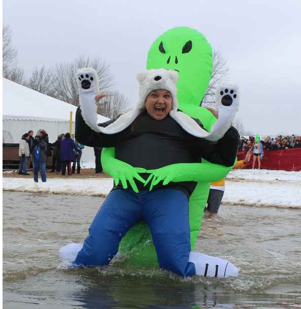 A person is waist deep in water wearing an alien costume and bear hat smiles and looks at the camera