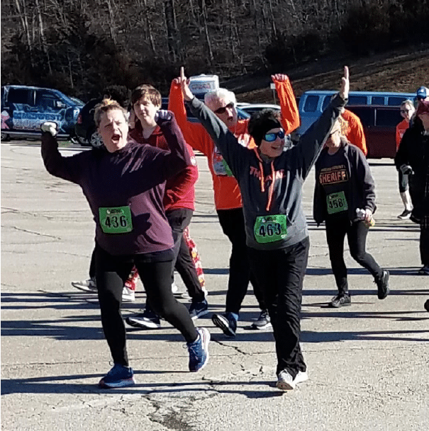 A group of people wearing racing bibs on their shirt have their hands in the air and scream for joy