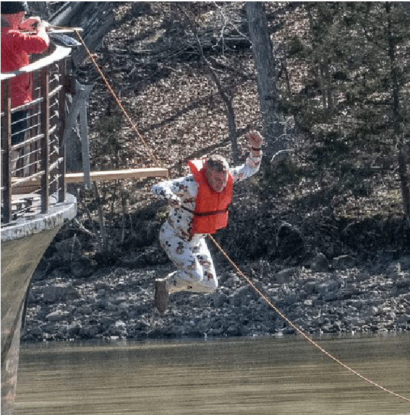 A person jumps off a plank into the water while wearing a life jacket