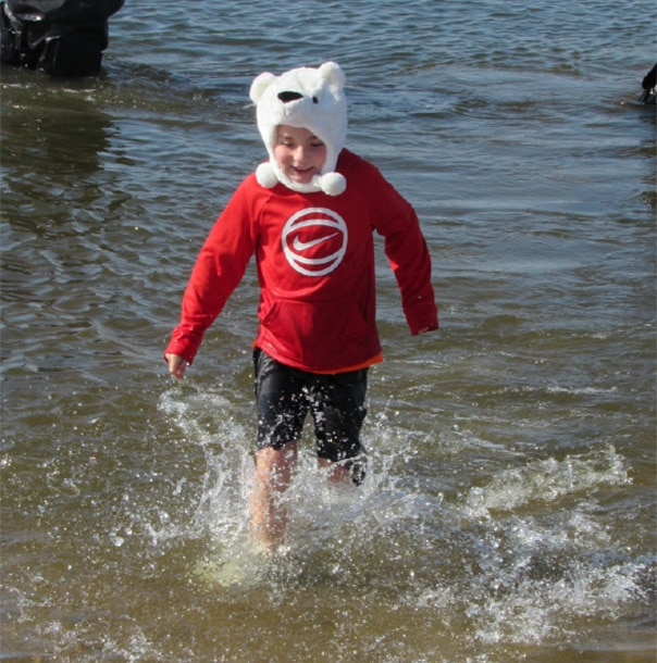 A young Polar Plunger wearing a bear hat runs out of the water