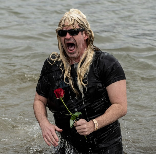 A Polar Plunger, wearing sunglasses and carrying a rose, stands in water and screams