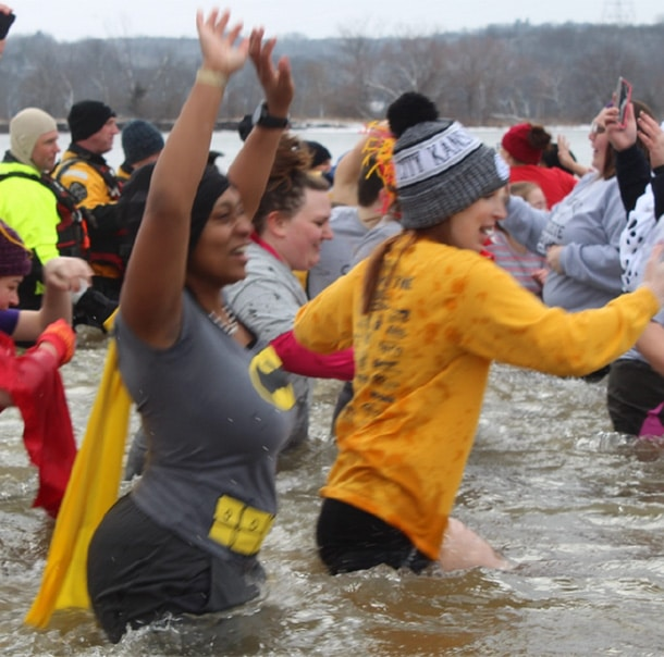 A large group of people run into water with their hands in the air