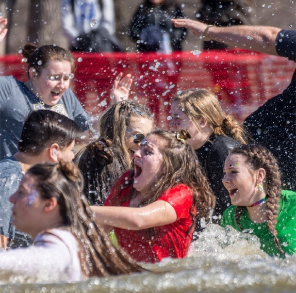 A group of Polar Plungers scream and thrash in the water