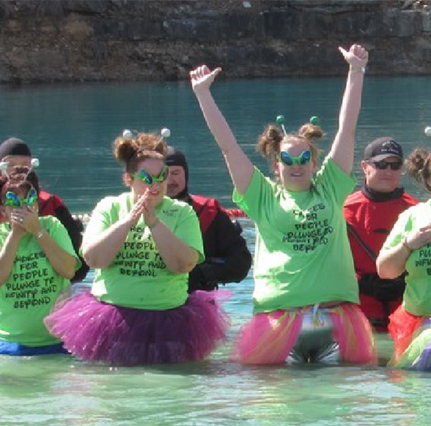 A group of Polar Plungers stand in waist-deep water with their hands raised