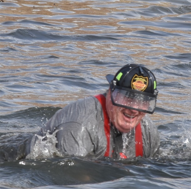 A Polar Plunger covered in water from the waist down while wearing a firefighter helmet smiles