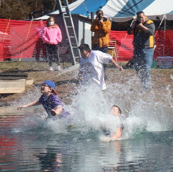 A group of people jump into water resulting in a huge splash