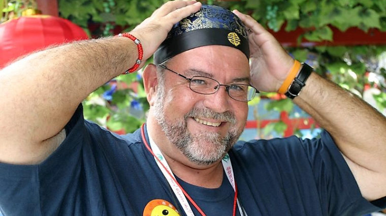 Gary Brimer wears a smiley face sticker and a bandana while smiling at the camera
