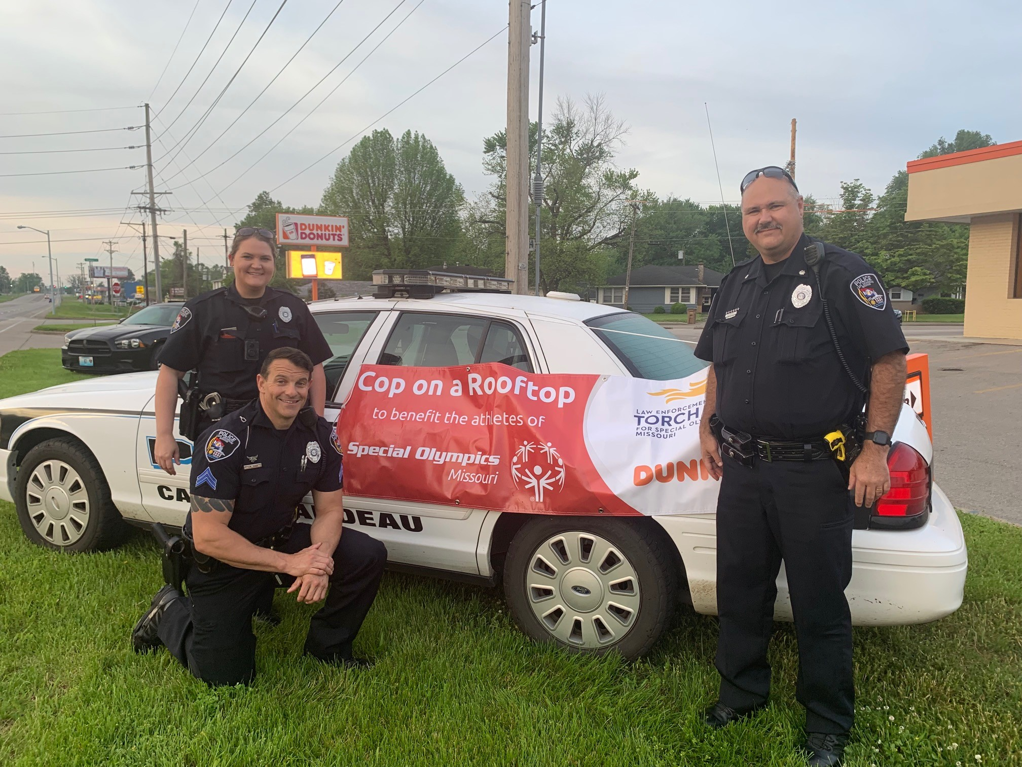 """Three law enforcement officers pose in front of a cop car with a """"Cop on a Rooftop"""" banner"""