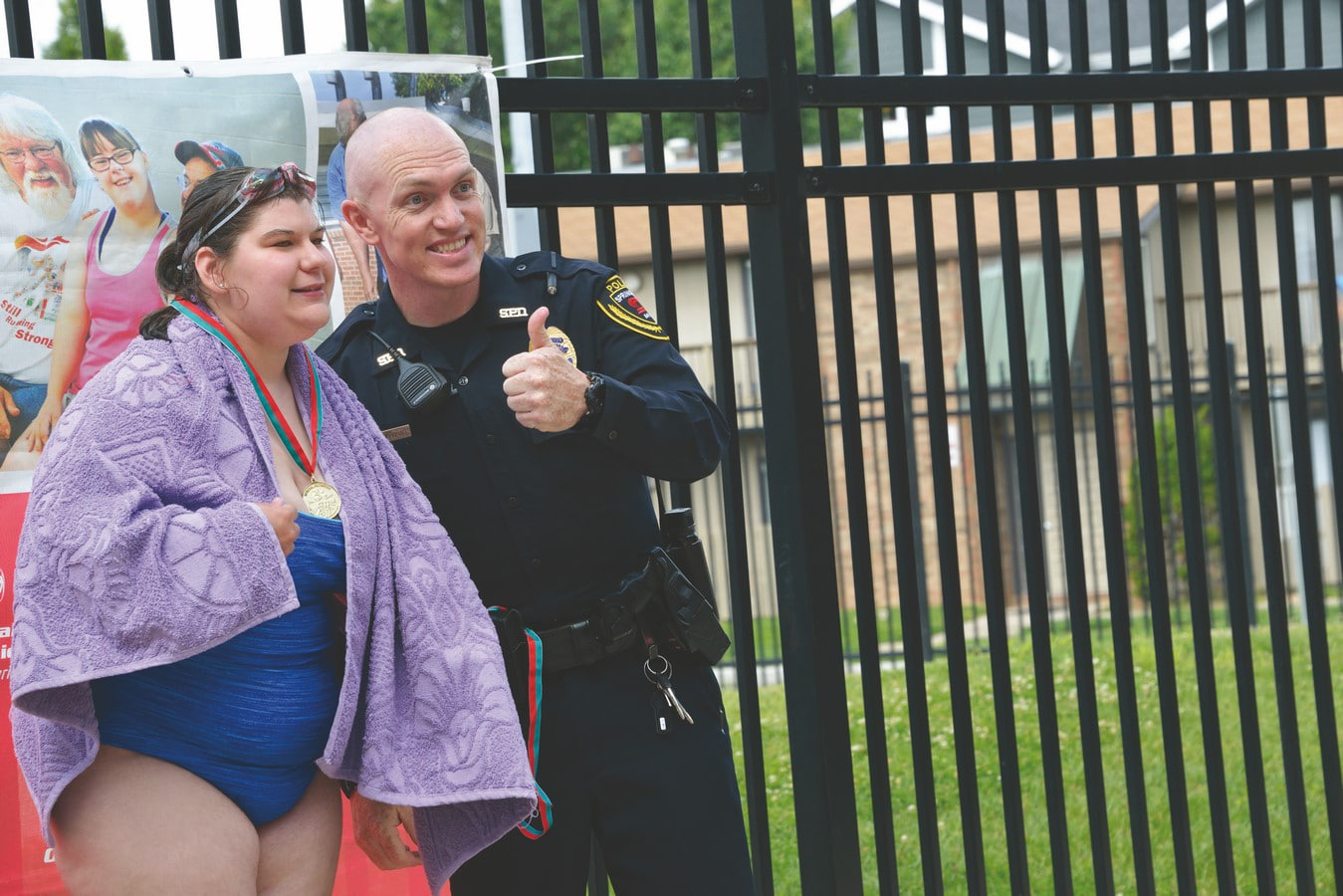 Aquatics athlete with gold medal around neck poses with police officer with their thumb up