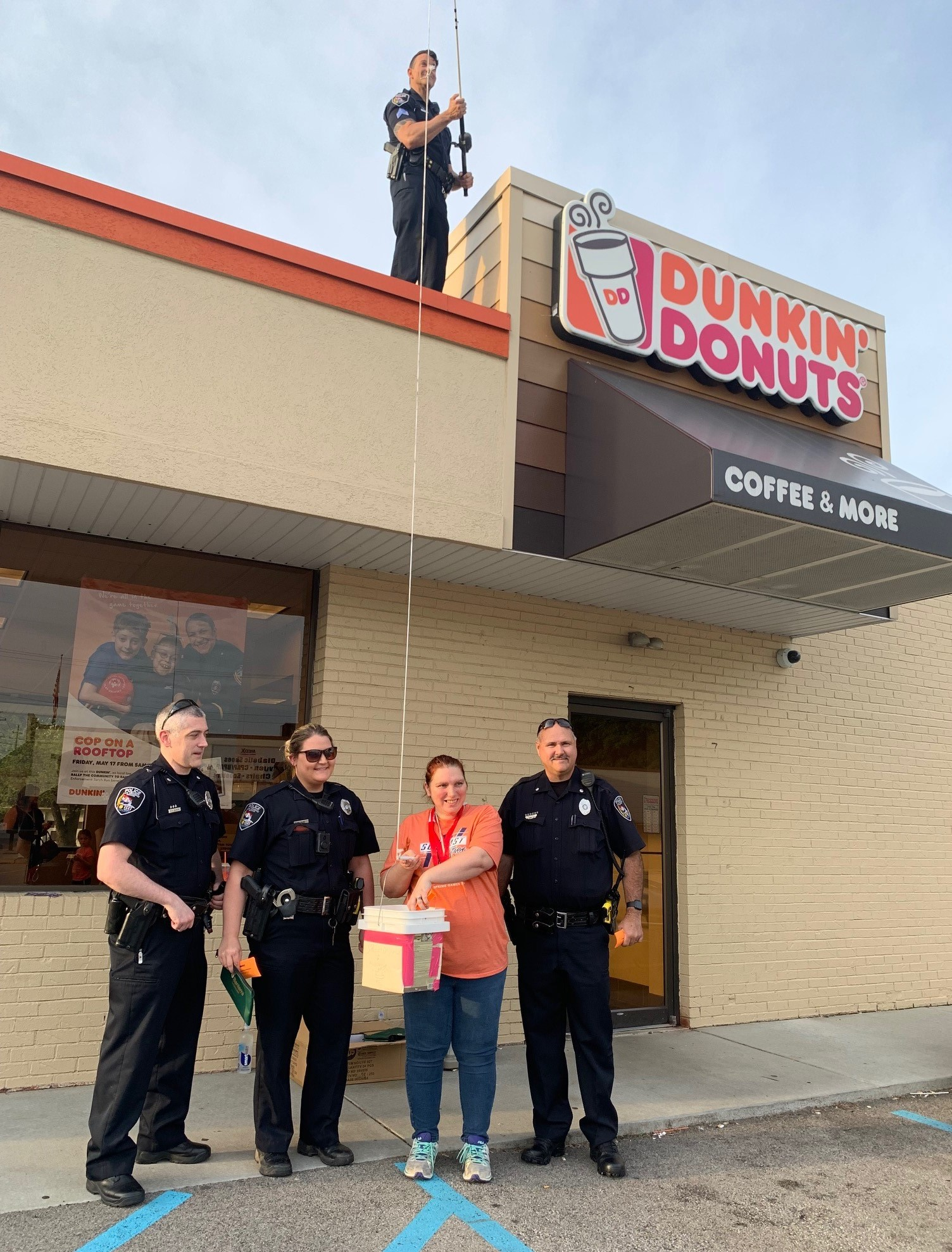 A law enforcement officer stands on the roof of a Dunkin' Donuts holding a tip jug on a fishing line with an athlete and other officers on the ground