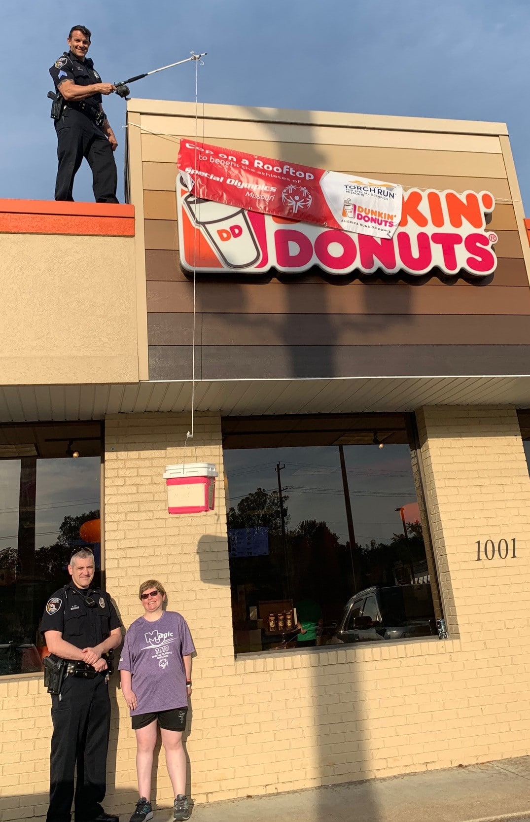A law enforcement officer stands on the roof of a Dunkin' Donuts holding a tip jug on a fishing line