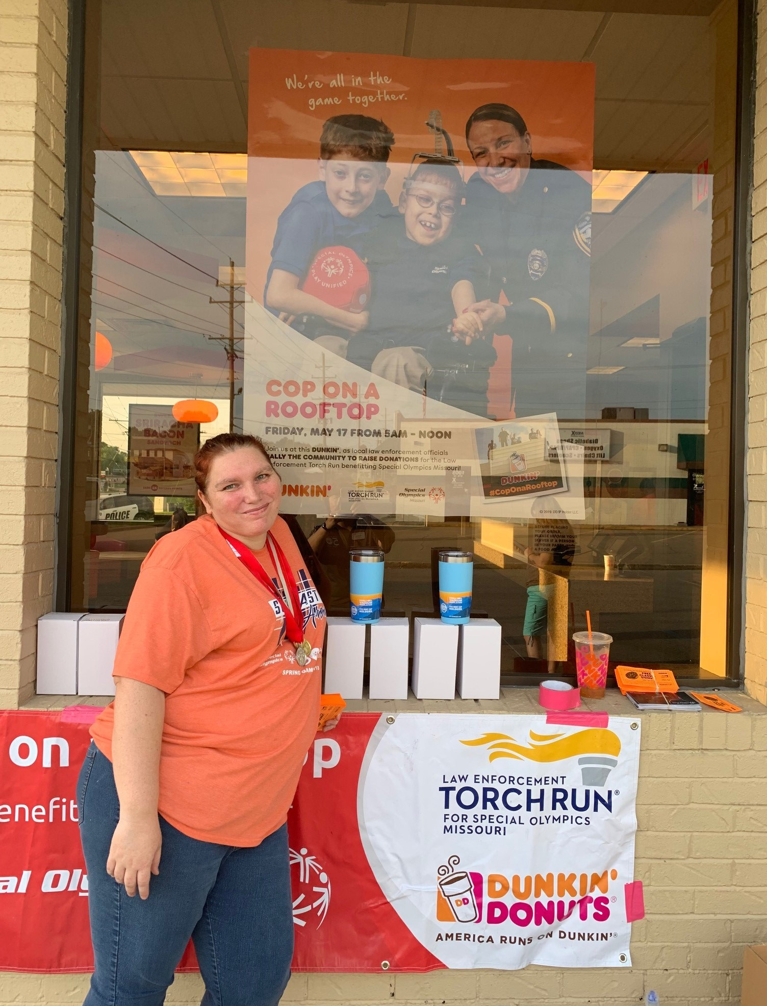 An athlete poses for a photo outside Dunkin' Donuts with a banner and giveaway mugs