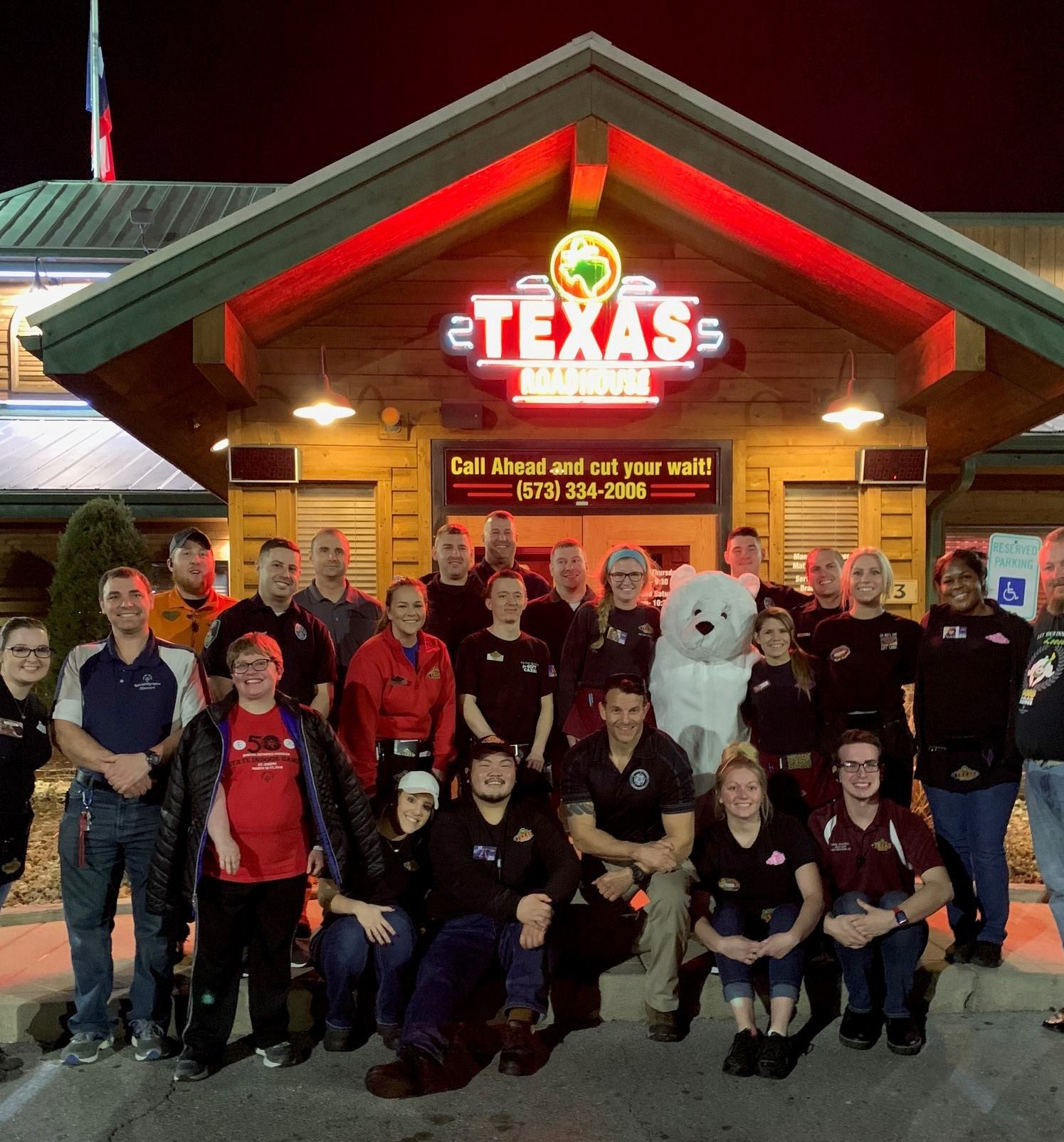 A group of law enforcement officers and servers pose for a photo outside of a Texas Roadhouse