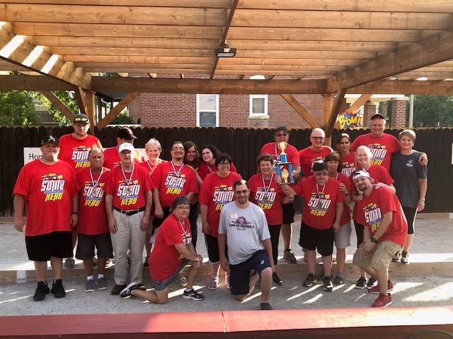 A group of athletes and volunteers pose for a photo on an outdoor bocce court