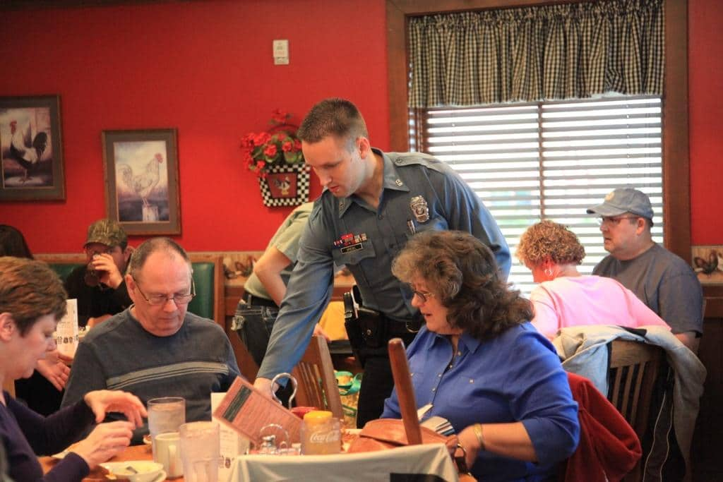 A law enforcement officer serves food to a group of people in a restaurant