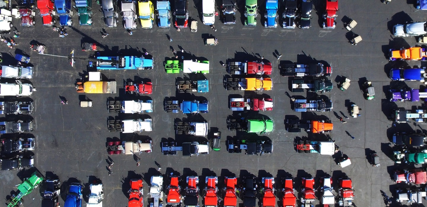 An aerial photo of more than 50 semi trucks sit in a parking lot