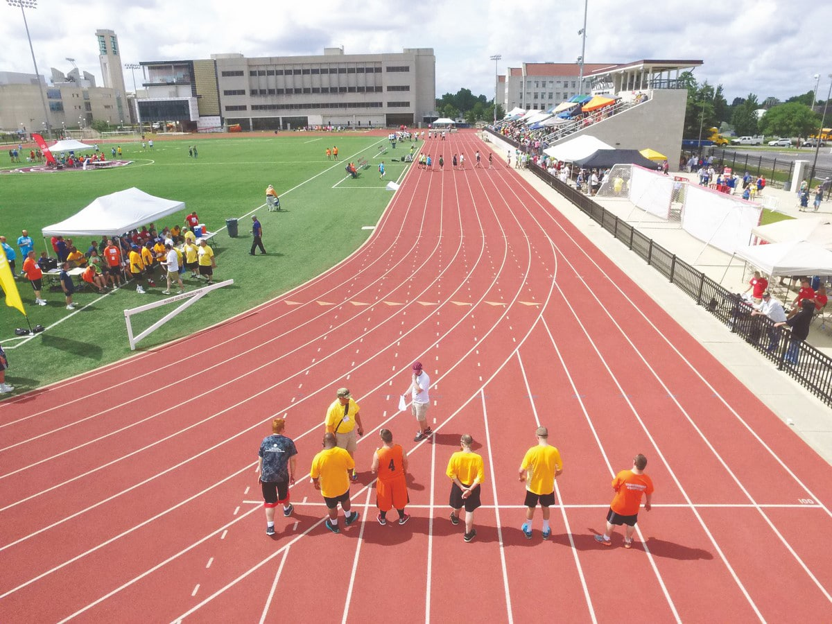 Aerial photo of the back of athletes on a track getting ready to race