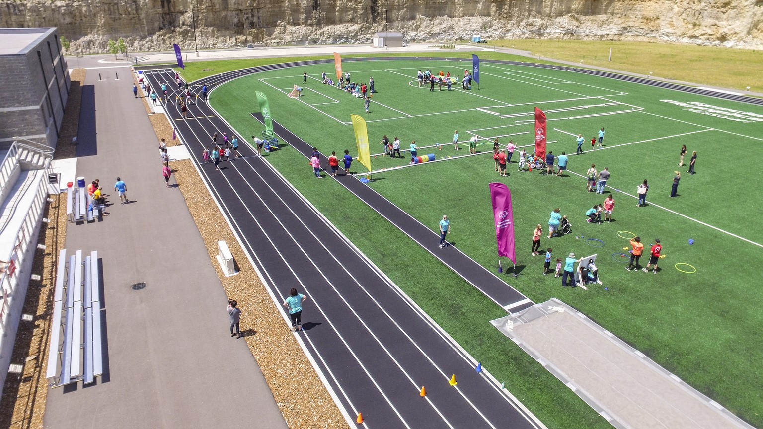 An aerial photo shows a group of Young Athletes and volunteers playing on the turf field at the Training for Life Campus