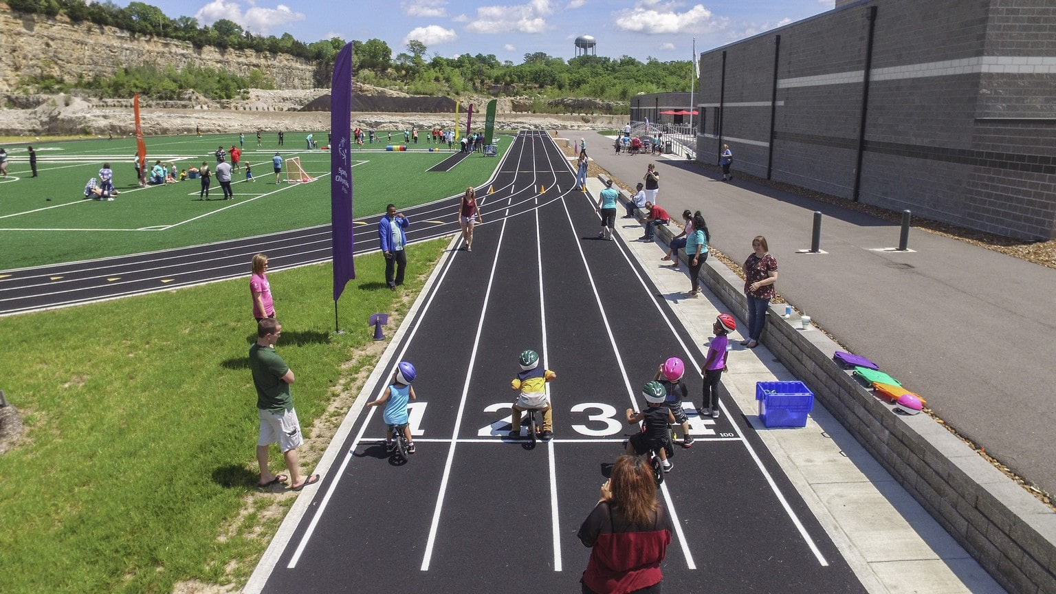 An aerial photo shows a group of Young Athletes riding Strider bicycles down the track
