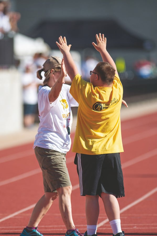 Volunteer walks out to high-five athlete standing on the track with their arms up