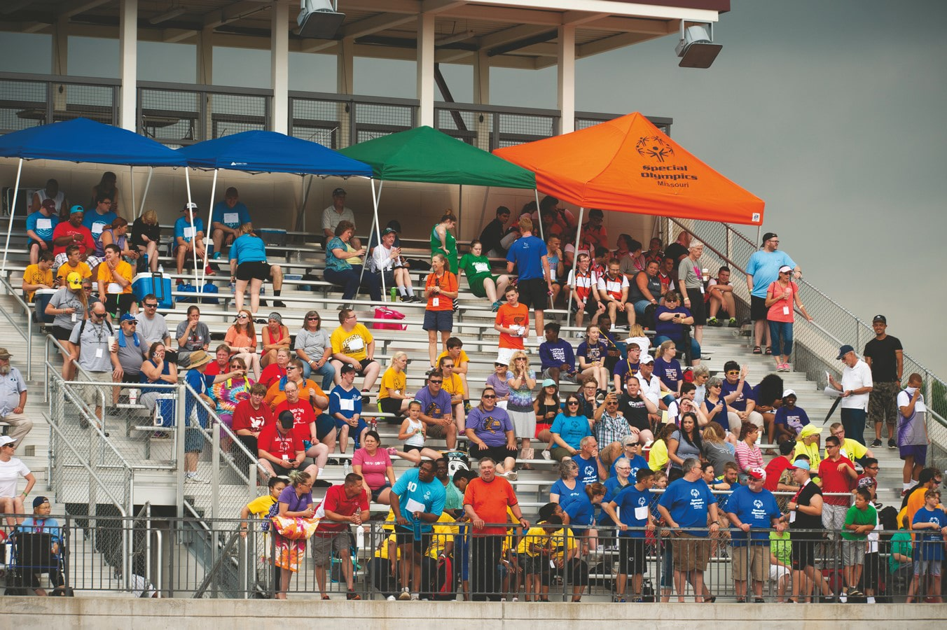 Large group of spectators sitting on bleachers watching and cheering on athletes