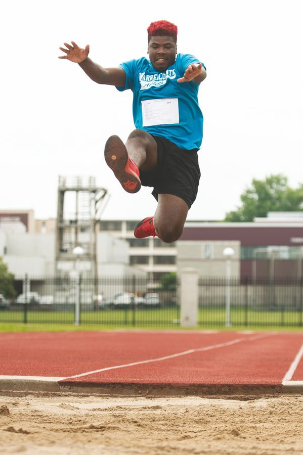 An athlete soars through the air during a long jump competition