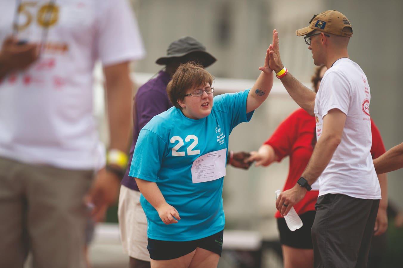 Athlete in blue shirt high-fives volunteer