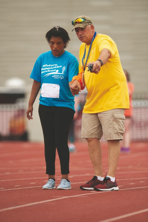 Volunteer holds athletes hand and points forward while standing on the track