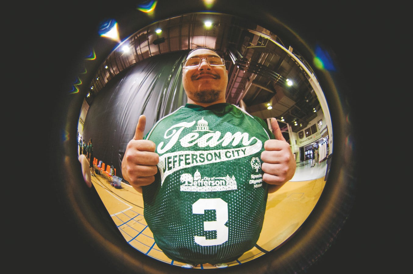 A circular fish eye photo of an athlete staring at the camera and holding their thumbs up