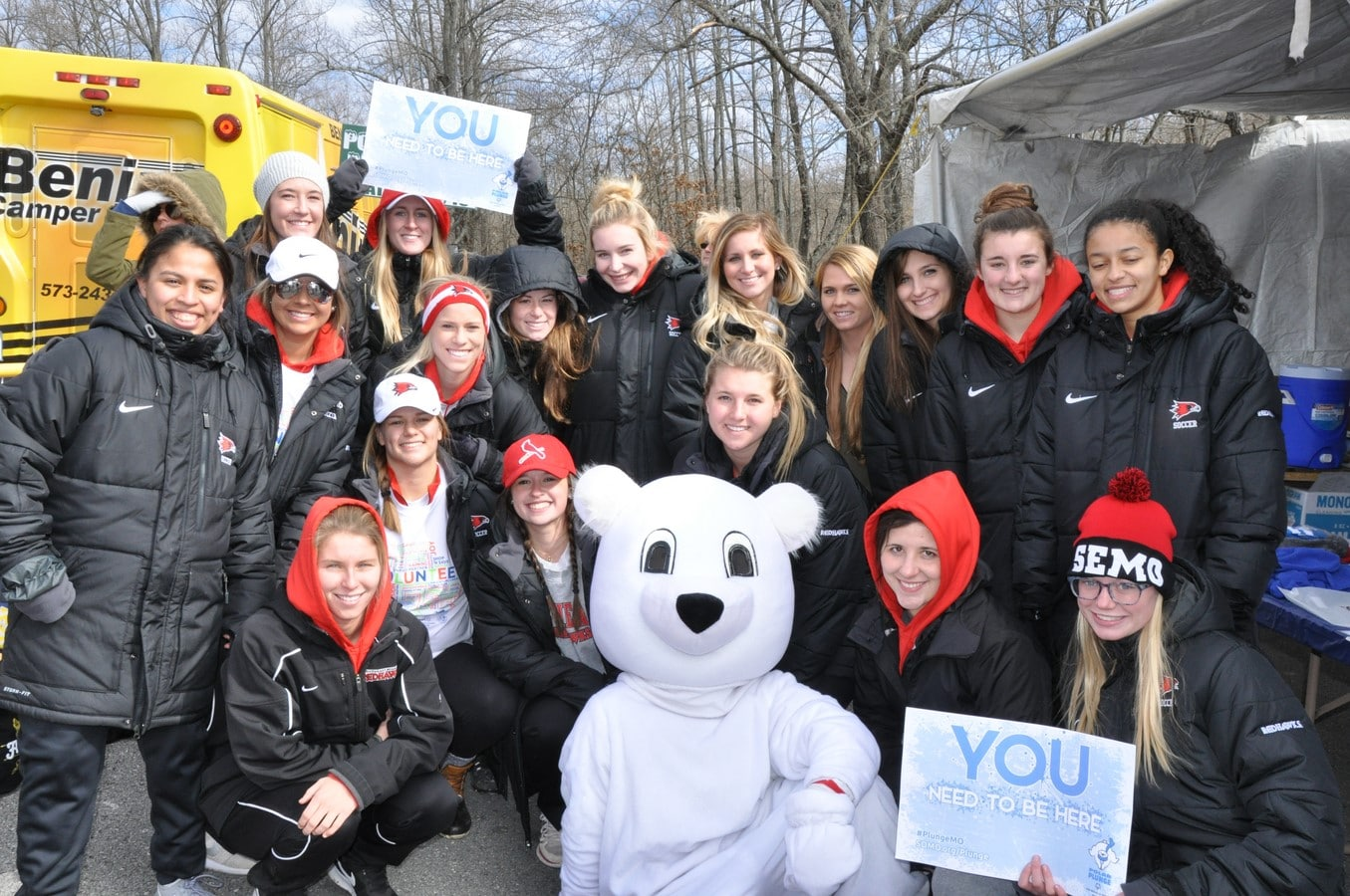 "A group of volunteers pose for a photo with someone in a polar bear costume holding signs that say ""You need to be here"""