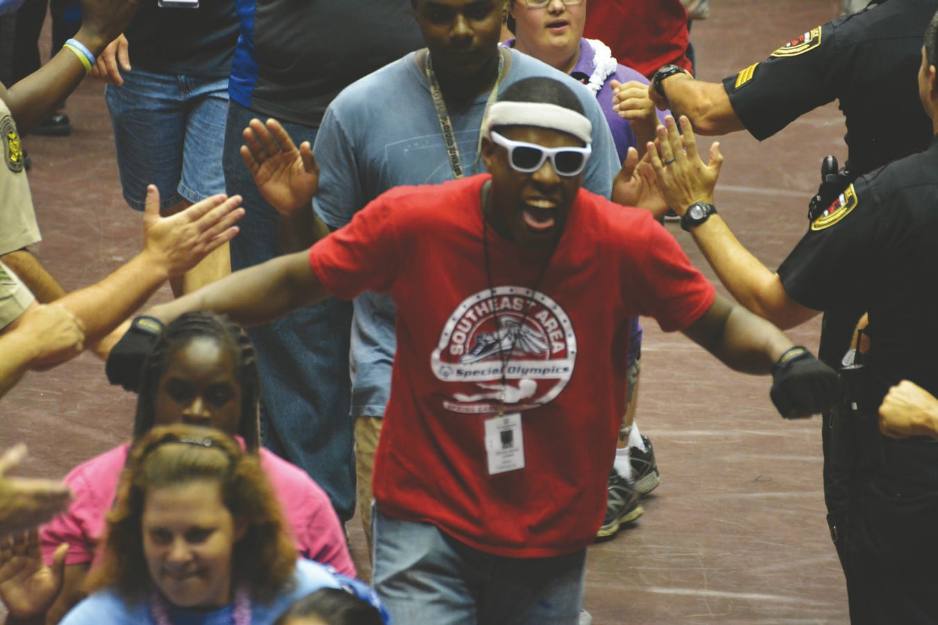 An ecstatic athlete with a big grin on their face runs through a tunnel of volunteers high-fiving them