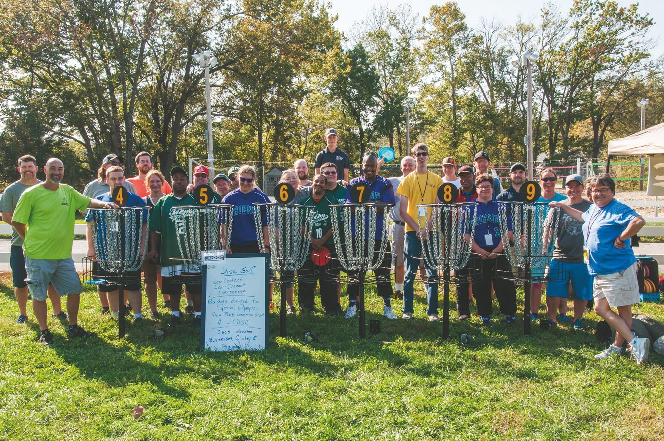 Group of athletes, volunteers, and SOMO staff members smile while posing together behind disc golf baskets