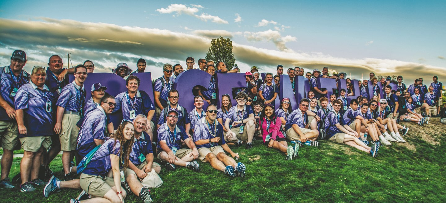 "A group of 100 athletes and volunteers pose for a photo on a grassy hill in front of large purple letters that spell out ""Rise with Us"""