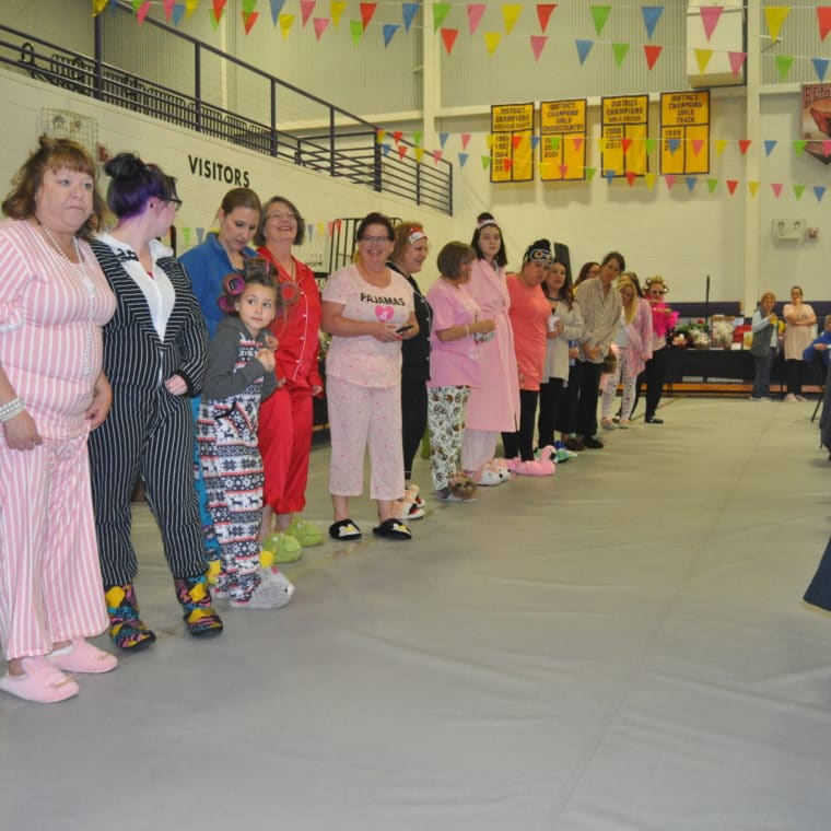 A group of people wearing pajamas form two lines and a tunnel