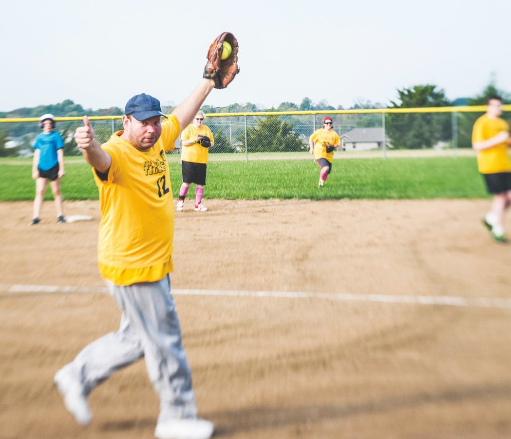 A softball athlete, ball in their glove, looks at the camera, smiles, and gives a thumbs up after making a catch while teammates look on in the background