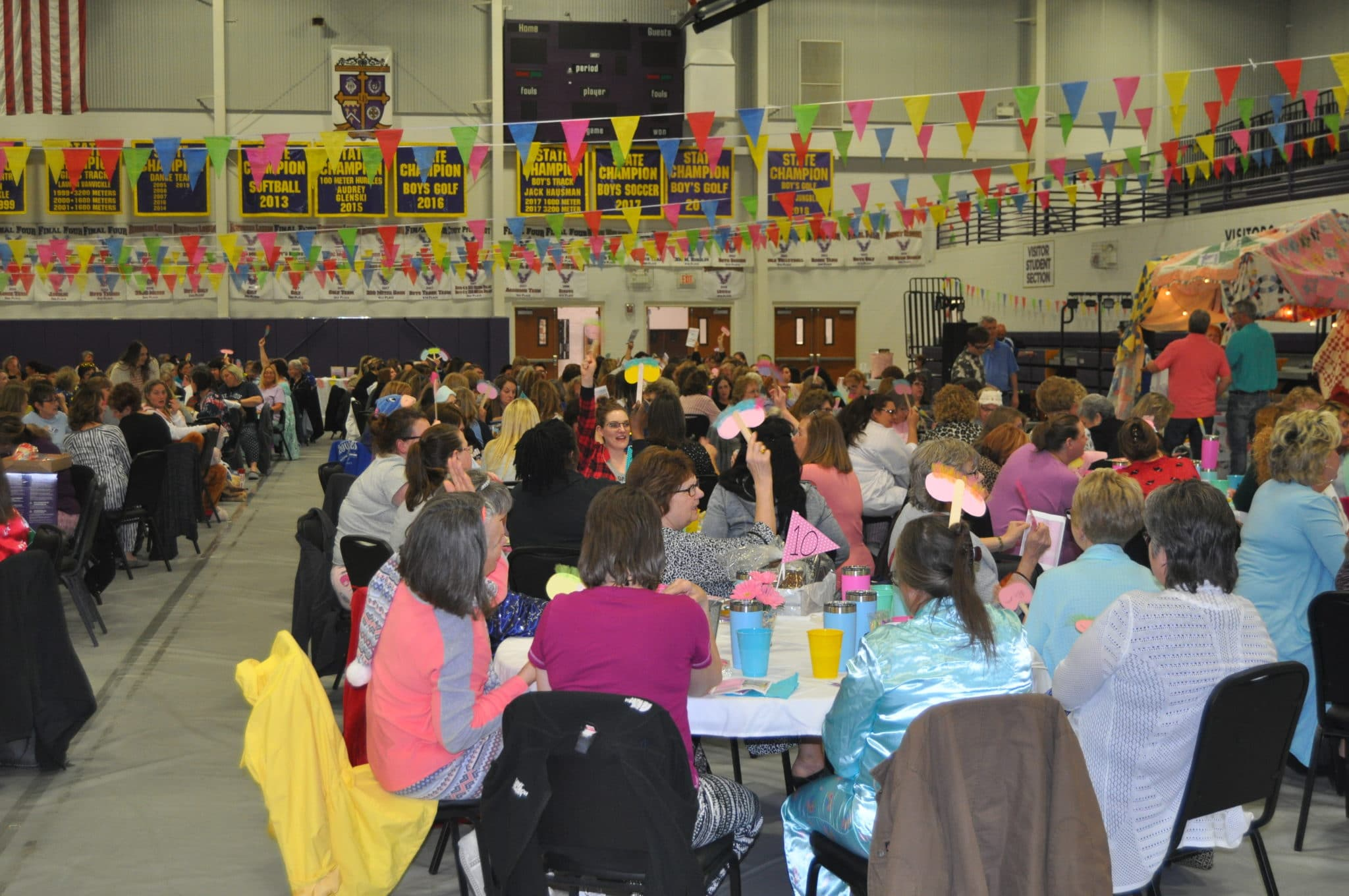 A large group of people sit around tables holding up auction paddles