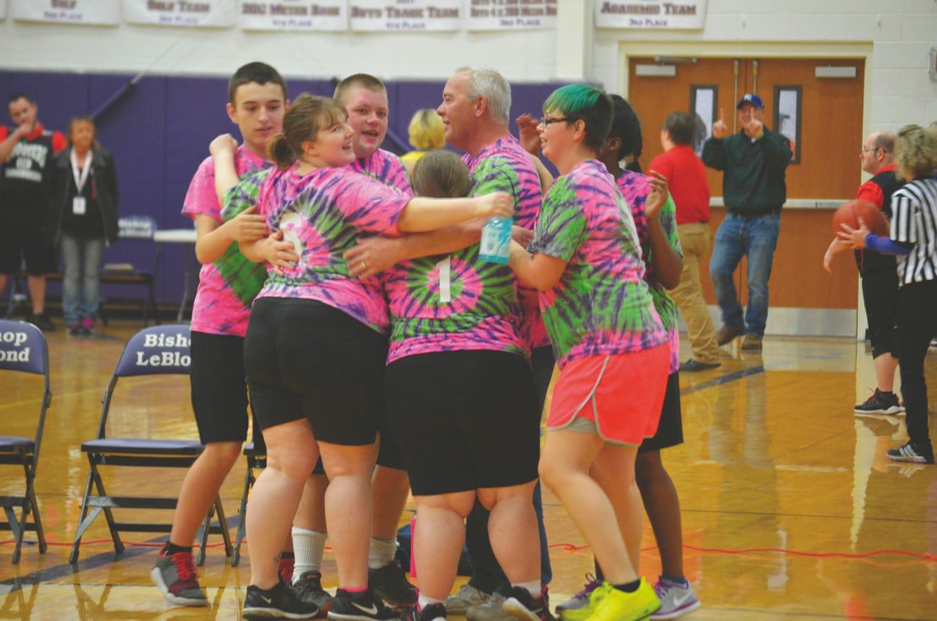 A basketball team wearing pink, purple, and green tie-dye uniforms take a moment for a group hug on the court