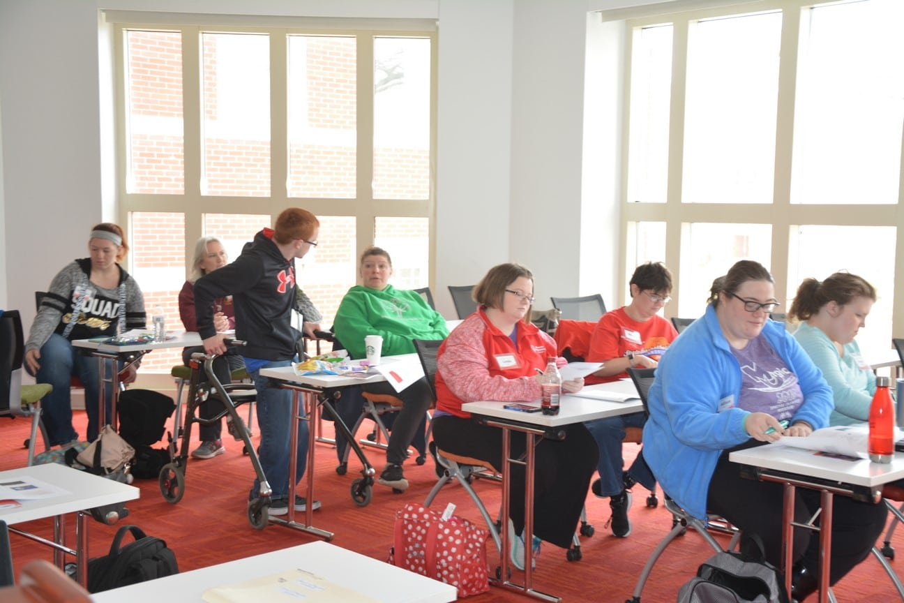 A group of athlete-leaders and mentors pay attention during an Athlete Leadership class