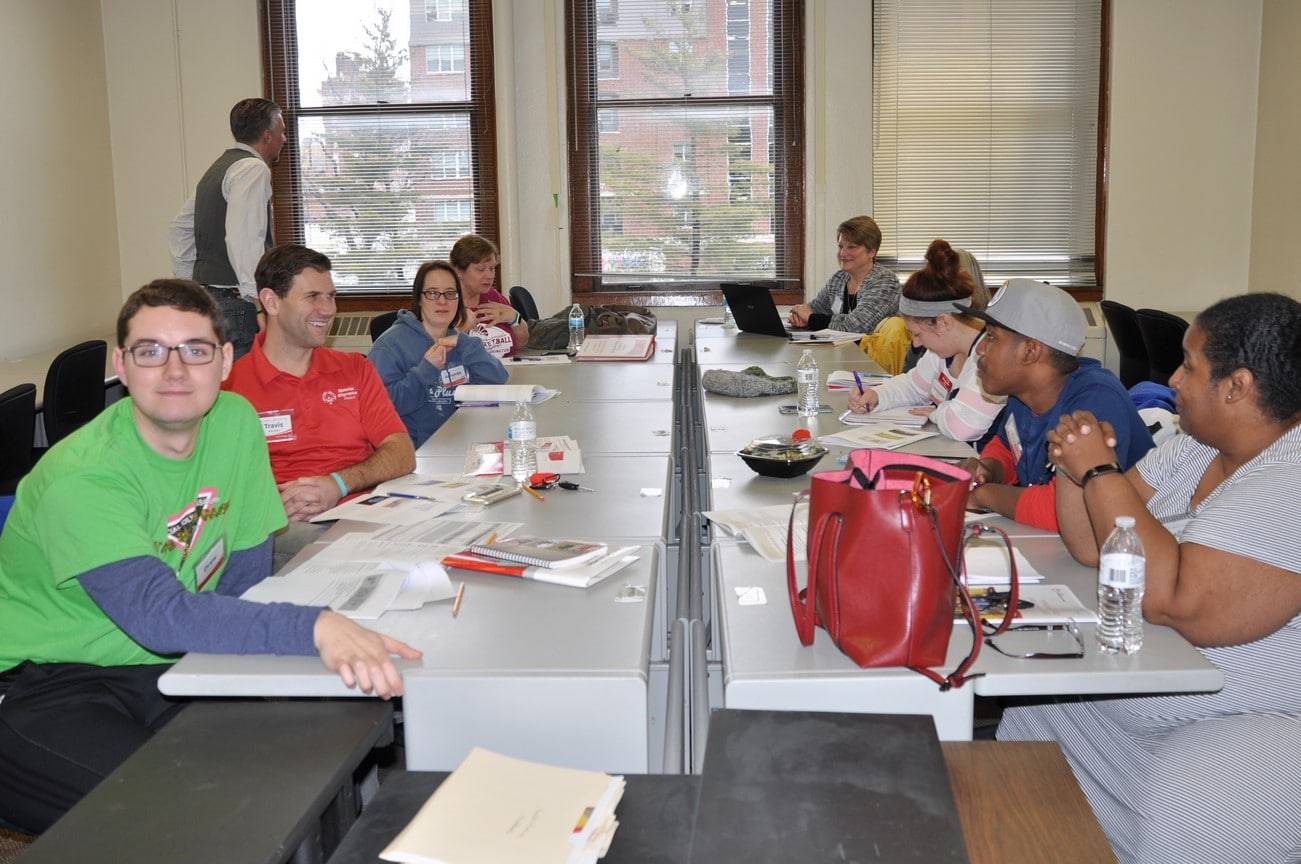A full class of athlete-leaders and mentors sit at a large table during a break of an Athlete Leadership class