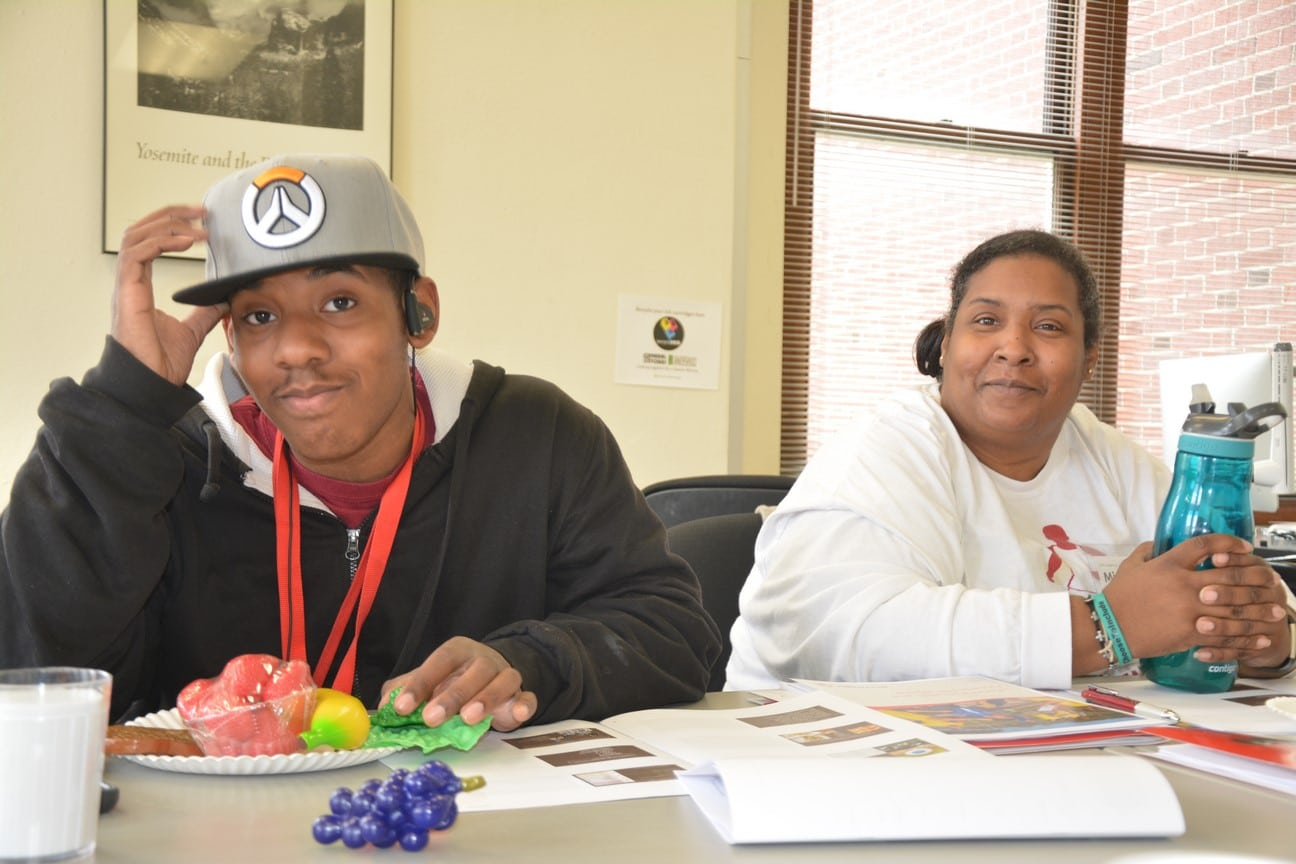 An athlete-leader and mentor look into the camera with a plate of plastic fruit in front of them during an Athlete Leadership class