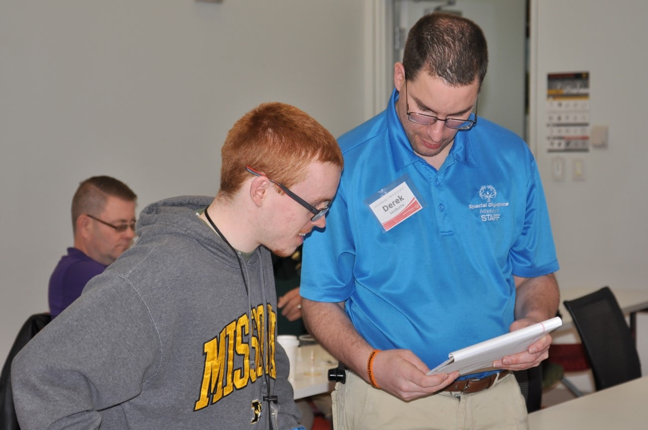 An instructor shows a pad of paper and talks to an athlete-leader during an Athlete Leadership class