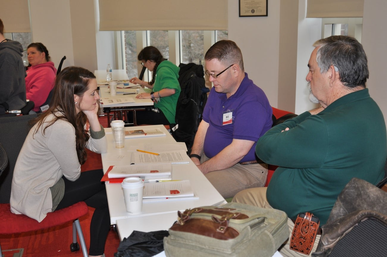 An instructor chats with an athlete-leader and their mentor during class