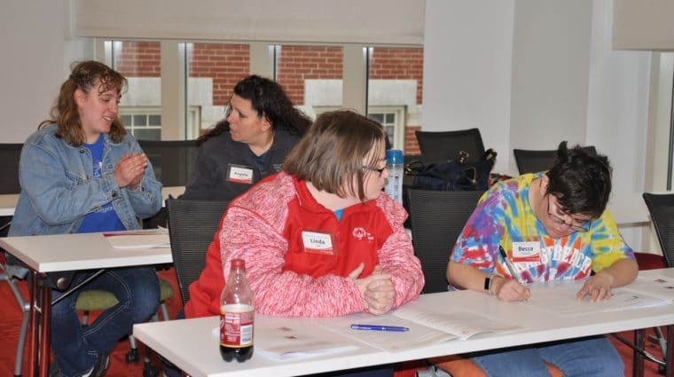 Athlete-leaders and mentors work on writing speeches during an Athlete leadership class