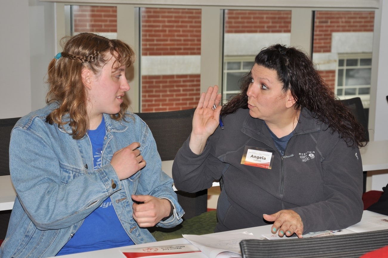 An athlete talks to their mentor during an Athlete Leadership class