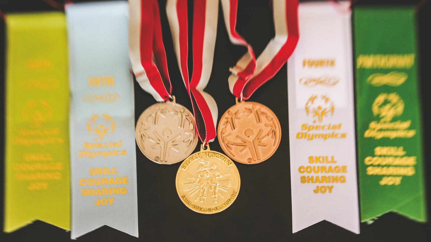 white, yellow, and green ribbons lay on a table with a silver, gold, and bronze medal