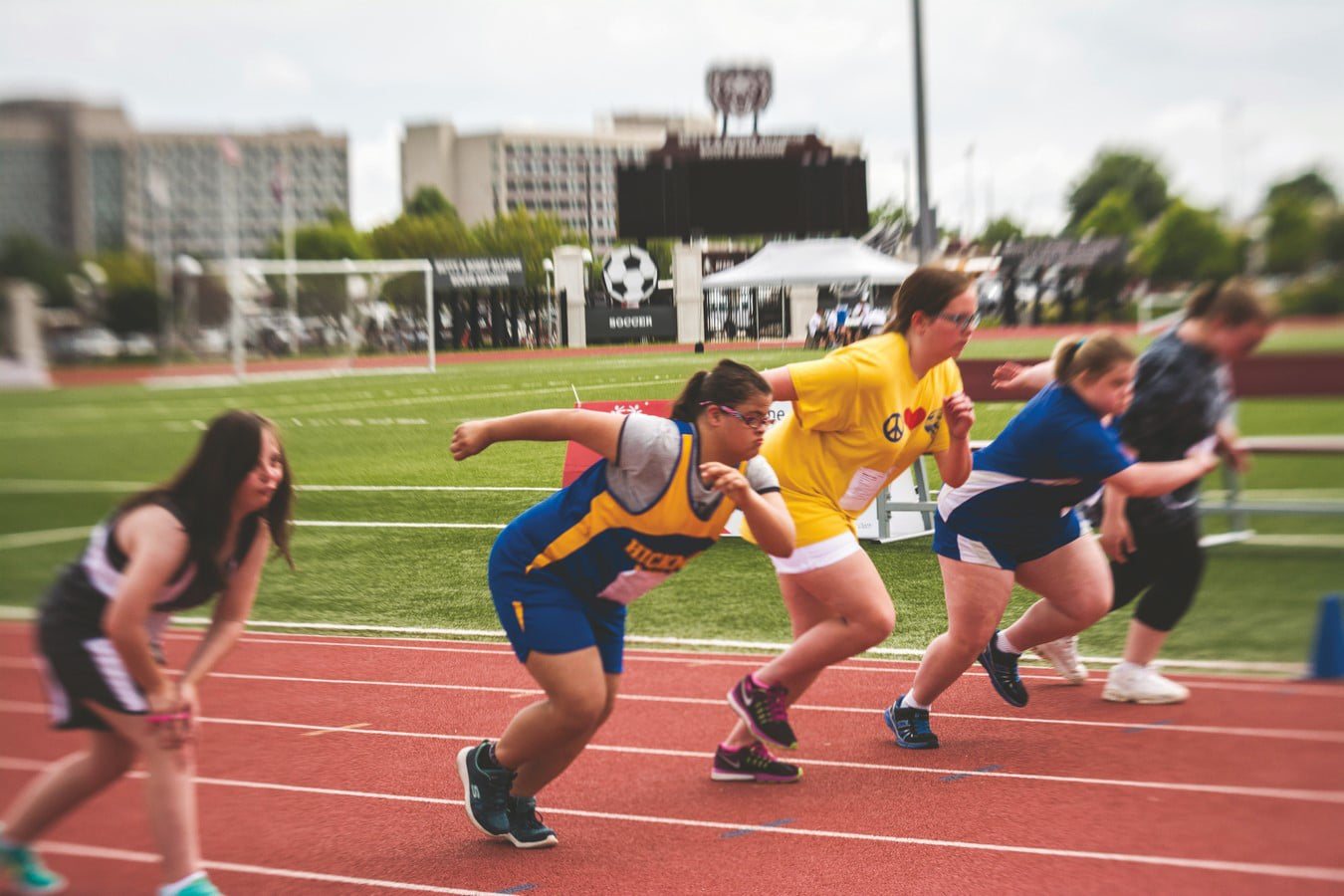 A group of five athletes break off the starting line during a track race